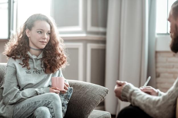 Aliviado com o aconselhamento. adolescente cacheado agradável e atraente sentindo-se aliviado durante o aconselhamento