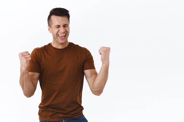 Aliviado, satisfeito, homem bonito feliz comemorando uma ótima notícia