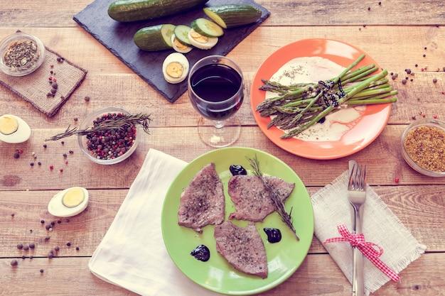 Almoço com bifes, espargos e vinho
