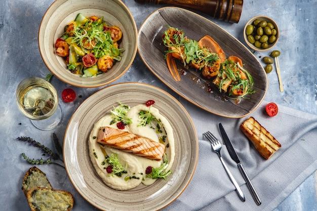 Almoço conjunto salmão grelhado com salada de camarão purê de legumes rolo de vinho branco vista superior