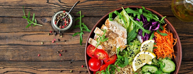 Almoço da bacia de buddha com galinha e quinoa grelhados, tomate, guacamole e arugula. top vie