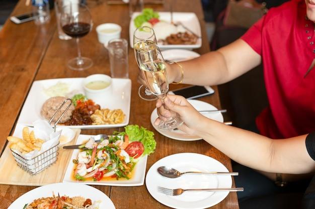 Almoço da celebração dos amigos com as mãos que brindam o vinho spakling de vidro com alimento.