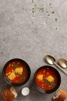Almoço de dieta de sopa de tomate com milho e ervas.