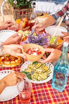 Almoço de domingo para família caucasiana sentada em uma mesa de madeira legumes e pizza na mesa