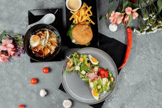 Almoço de negócios com três pratos. almoço com hambúrguer macarrão asiático e salada caesar.