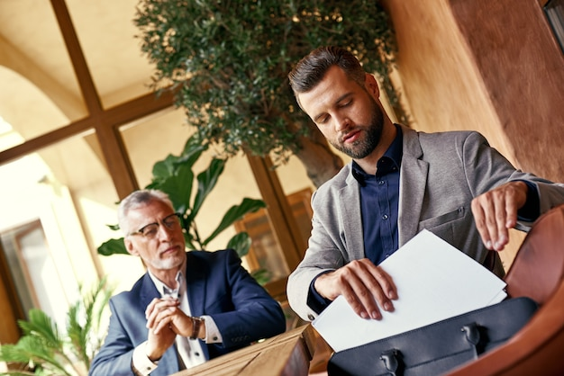 Almoço de negócios dois executivos no restaurante sentados à mesa um homem assinando contrato