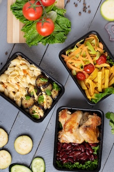 Almoço de negócios em caixas de comida, asas de frango assado, legumes cozidos no vapor, carne cozida, refeição pronta para comer