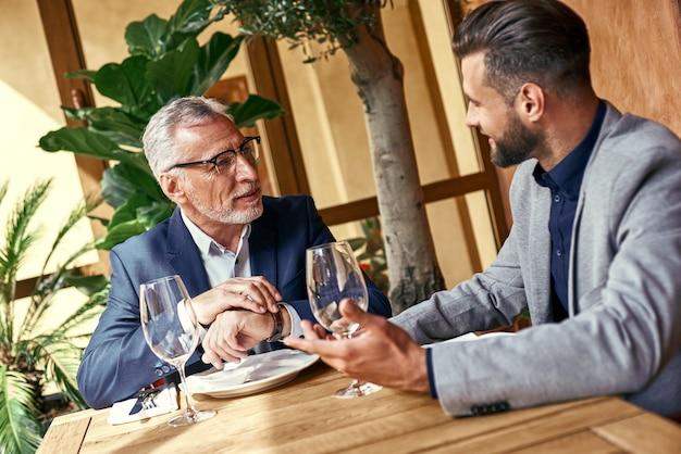 Almoço de negócios para dois executivos no restaurante sentados à mesa discutindo equipe alegre do projeto