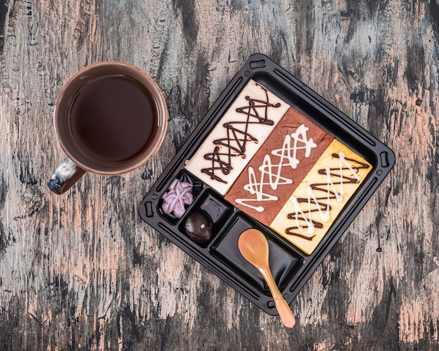 Almoço doce com bolos multicoloridos e vista superior do café em fundo escuro
