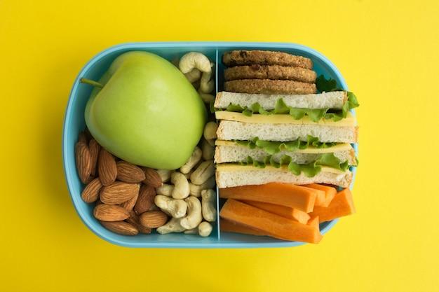 Almoço na caixa azul no centro do fundo amarelo
