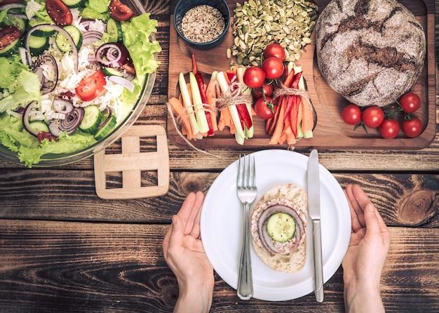 Almoço na mesa com comida diferente, mãos femininas com um prato
