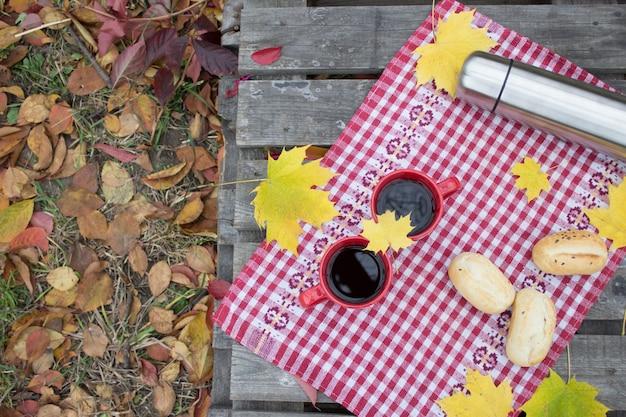 Almoço na natureza, romance de outono. dois copos vermelhos e uma garrafa térmica com uma bebida quente