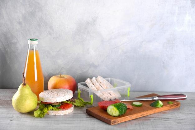 Almoço para o seu filho na escola, caixa com um sanduíche saudável e salada de frutas e suco de maçã na garrafa para beber