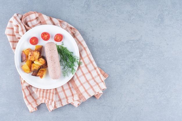 Almoço perfeito. batatas fritas e linguiça cozida no prato branco
