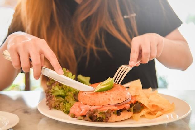 Almoço rápido. bagel de salmão defumado com salada e batatas fritas