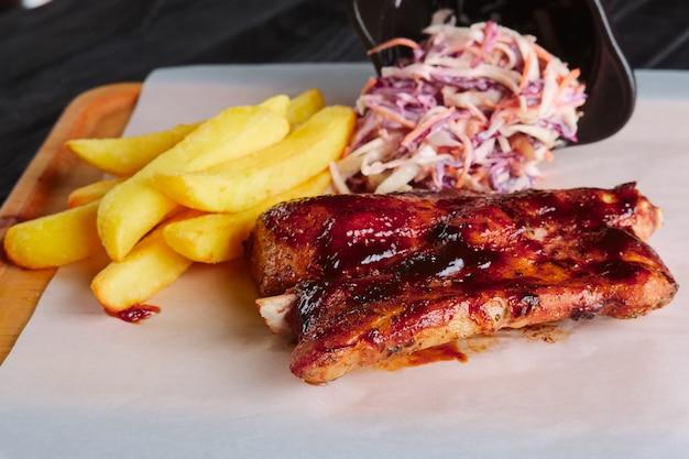 Almoço ruskic. costelas grelhadas com batata frita e salada de repolho roxo