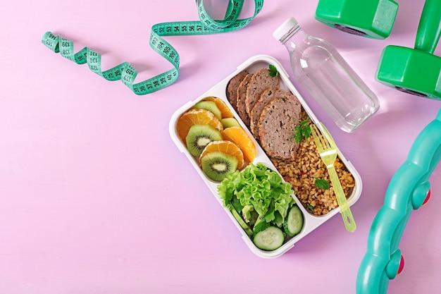 Almoço saudável com bulgur, carne e legumes frescos e frutas em um fundo rosa.