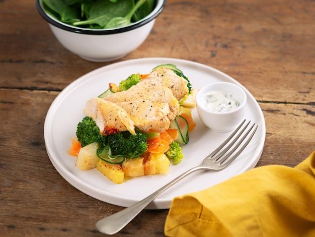 Almoço saudável, jantar. peito de frango cozido saudável com legumes, batatas grelhadas, pepino, cenoura, brócolis e espinafre em um prato em estilo rústico.