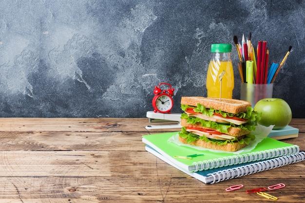 Almoço saudável para a escola com sanduíche, maçã fresca e suco de laranja.