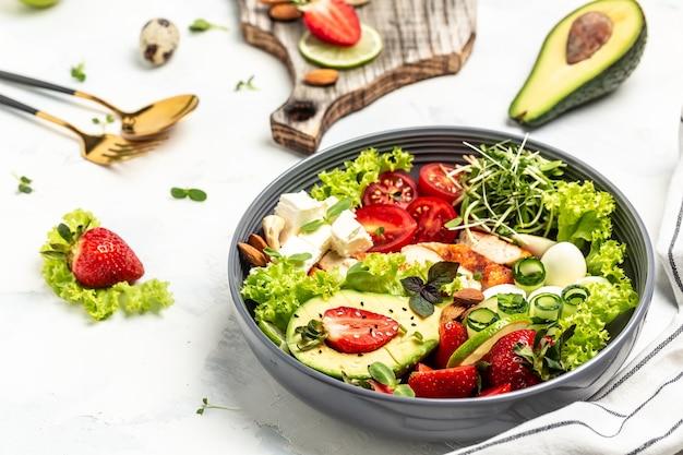 Almoço saudável tigela de buda de vegetais com frango grelhado e abacate, queijo feta, ovos de codorna, morangos, nozes e alface em fundo branco. vista do topo.
