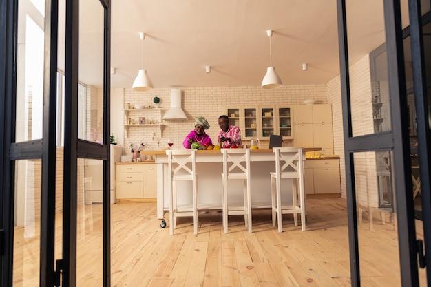 Almoço saudável. vista superior de pessoas agradáveis e felizes cortando legumes em pé na cozinha