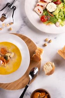 Almoço sopa de frango com croutons e salada de peito de frango e vinho sobre um fundo claro