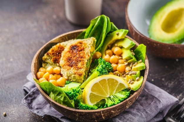 Almoço vegano em uma tigela de coco: hambúrgueres verdes com salada e grão de bico.