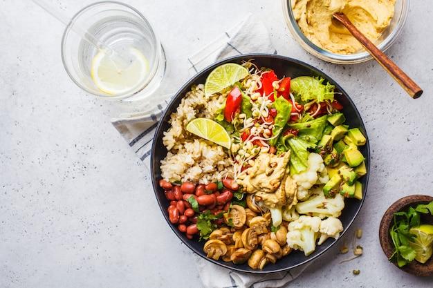 Almoço vegetariano. arroz integral com cogumelos, feijões, salada e hummus na placa preta, eatind limpo.