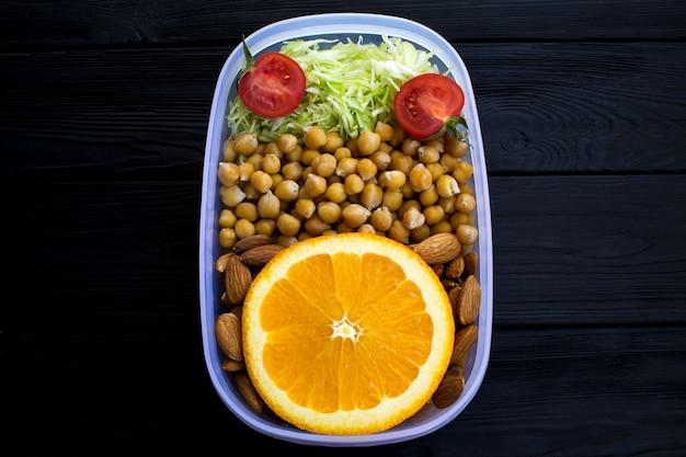 Almoço vegetariano com grão de bico na caixa no fundo preto de madeira