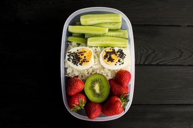 Almoço vegetariano na caixa no fundo preto de madeira