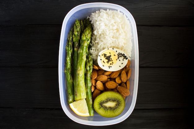 Almoço vegetariano na caixa sobre o fundo preto de madeira. vista superior.