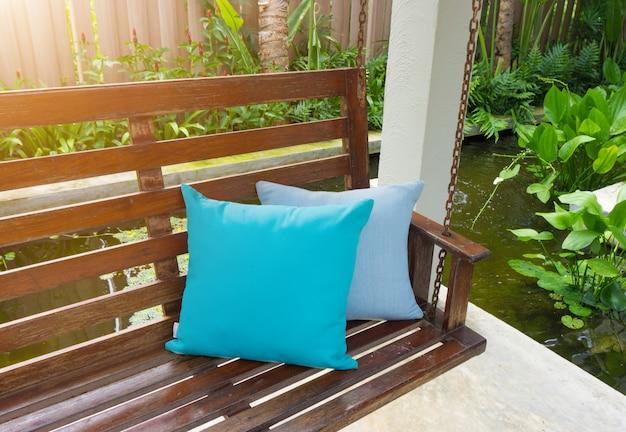 Almofada azul colocado em um balanço de madeira no resort.