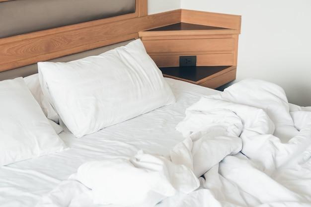 Almofada branca com cama amarrotada