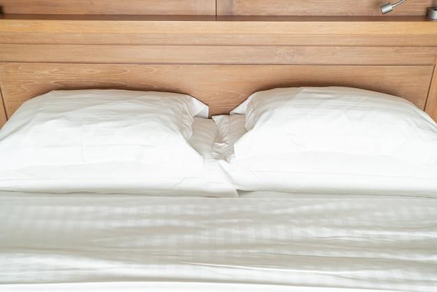 Almofada branca no interior de decoração de cama de quarto de hotel