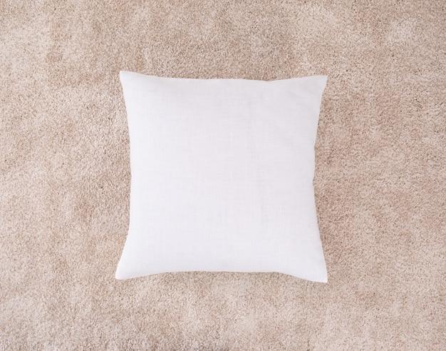Almofada branca no tapete marrom. um travesseiro com estojo de estopa.
