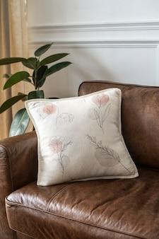 Almofada com arte de linha floral mínima em um sofá de couro