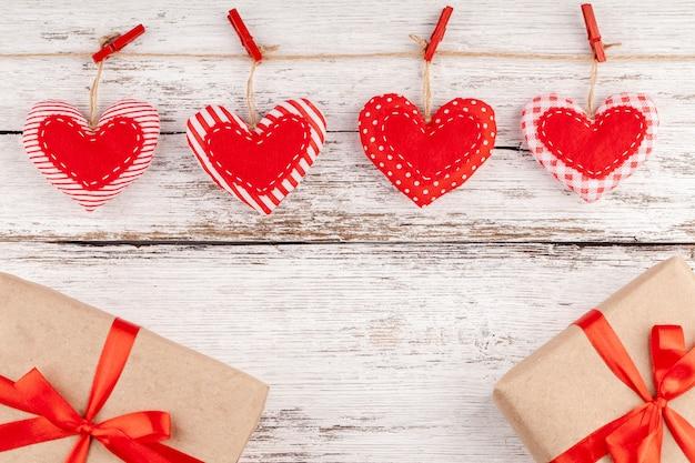 Almofada costurada linha de corações fronteira de tecido vermelho, caixas de presente com fita vermelha