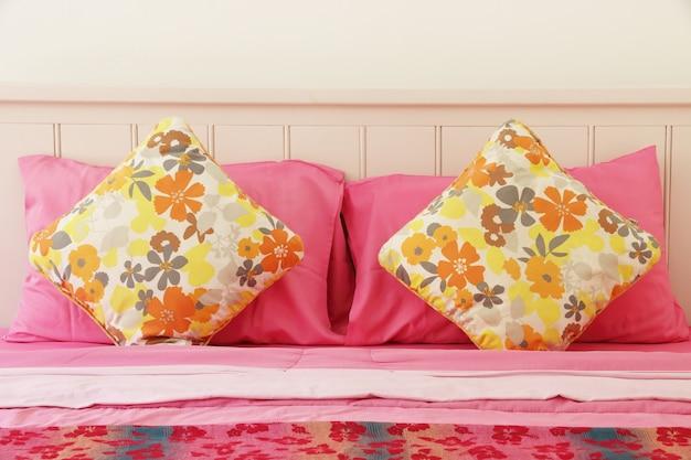 Almofada de polca colorida na cama-de-rosa