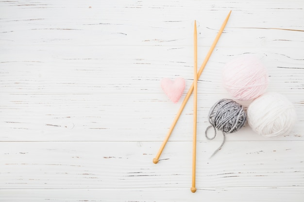 Almofada em forma de coração rosa; crochê e bola de fios no cenário de madeira