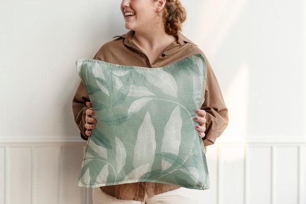 Almofada floral verde segurada por uma mulher, decoradora