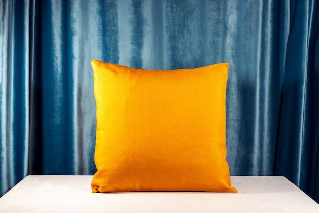 Almofada laranja na mesa branca