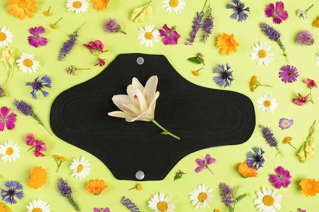Almofada menstrual reutilizável preta em superfície verde com flores silvestres naturais