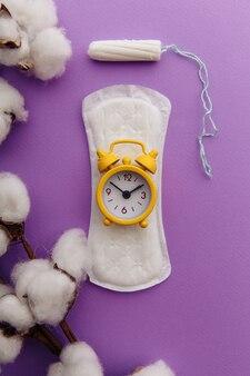 Almofada menstrual, tampão de algodão e despertador amarelo lilás