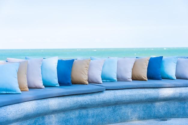 Almofada na cadeira ou no sofá ao redor do pátio ao ar livre com vista para o mar e a praia do oceano