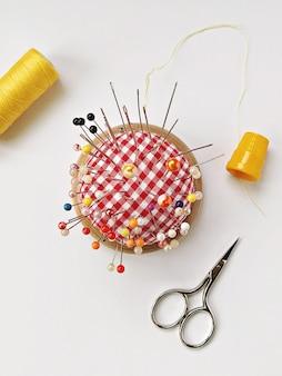 Almofada redonda de alfinetes com muitos alfinetes, dedal amarelo, carretel de linha e tesoura. acessórios de costura planos sobre fundo branco