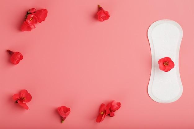 Almofada sanitária em um fundo rosa com uma flor vermelha na parte superior, com uma borda de flores para texto e imagens. espaço livre.
