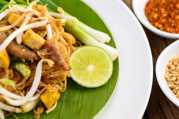 Almofada tailandesa em um prato branco com limão em uma mesa de madeira