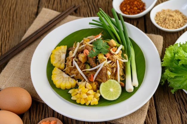 Almofada tailandesa em um prato branco com limão, ovos e temperos em uma mesa de madeira.