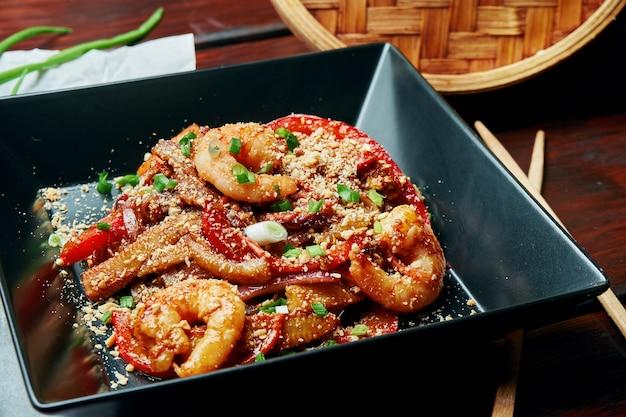 Almofada tailandesa ou phad tailandesa - um macarrão de arroz frito tradicional wok de prato tailandês com camarões e legumes em um prato preto sobre uma mesa de madeira. fechar-se