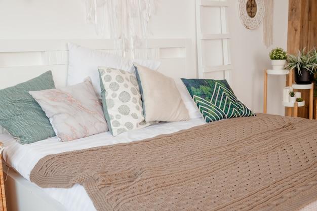 Almofada verde, bege na cama no quarto com lençóis de cor pastel na cama. design de apartamento elegante em estilo lagom. interior branco escandinavo elegante com cama, planta tropical, cobertor aconchegante.